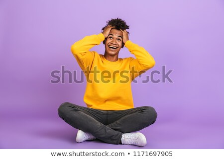 Portrait of surprised african american boy shouting and grabbing Stock photo © deandrobot