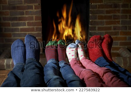 Stock photo: Family of feet warming at a fireplace