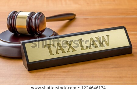 a gavel and a name plate with the engraving tax law stock photo © zerbor