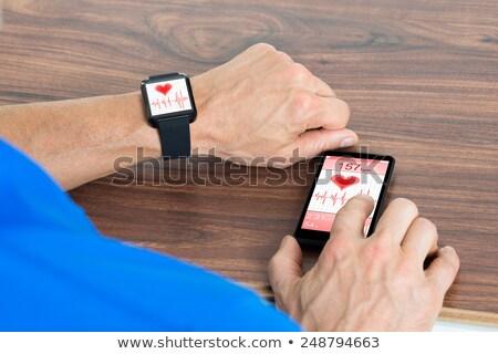 Uomo telefono cellulare frequenza cardiaca mano legno Foto d'archivio © AndreyPopov