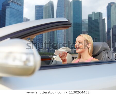 woman with smartphone in car over singapore city Stock photo © dolgachov