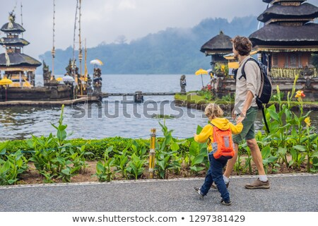 Boy traveler in the background of Pura Ulun Danu Bratan, Bali. Hindu temple surrounded by flowers on Stock photo © galitskaya