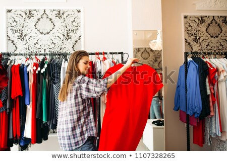 Fashionable woman in shirt holding and want buying elegant red dress. stock photo © studiolucky