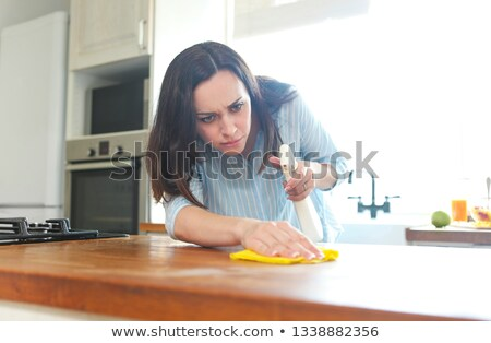 Woman with rag and spray bottle cleaning wooden counter-top Stock photo © dashapetrenko