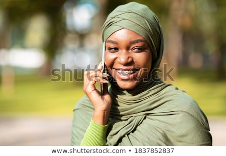 Young muslim businesswoman in hijab talking on smartphone outdoors Stock photo © pressmaster