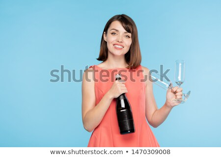 Happy gorgeous girl with toothy smile holding bottle of champagne and two flutes Stock photo © pressmaster
