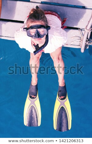 Young woman with mask sitting on the edge of the boat looking up Stock photo © boggy