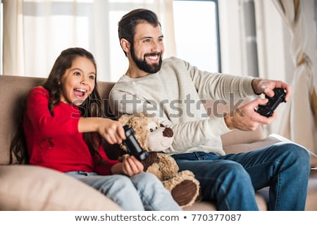 father and daughter playing video game at home Stock photo © dolgachov
