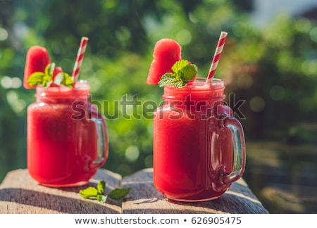 healthy watermelon smoothie with mint and striped straws against the background of greenery stock photo © galitskaya
