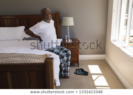 Stok fotoğraf: Front View Of A Senior African American Man Suffering From Back Pain In Bedroom At Home