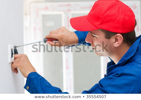 A young electrician installing an electrical switch in a new house Stock photo © galitskaya