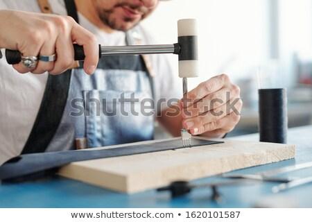 Hitting stitching chisel with hammer Stock photo © pressmaster