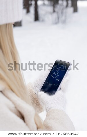Young blond woman in white fluffy knitted mittens looking for temperature Stock photo © pressmaster