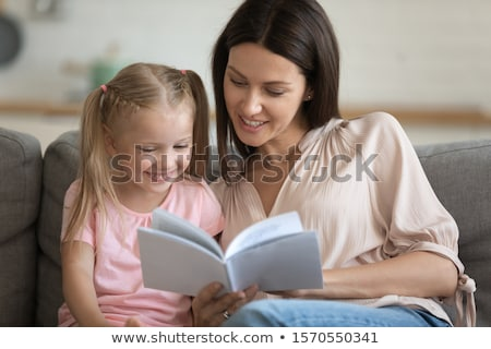 Young girl reading a book with the help of an adult Stock photo © photography33
