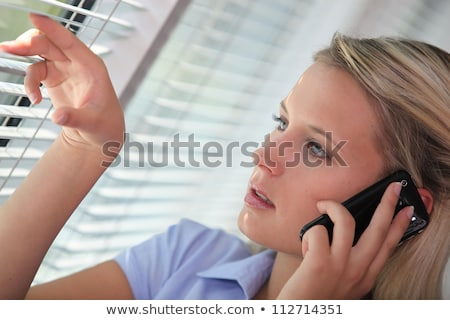 Woman on the phone looking through venetian blinds Stock photo © photography33