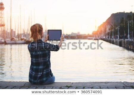 Young woman taking a photo with tablet pc Stock photo © pablocalvog