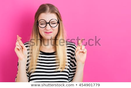 Young woman wishing with crossing fingers Stock photo © bmonteny