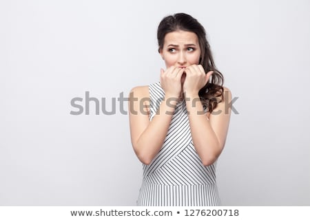 young woman biting her nails stock photo © deandrobot