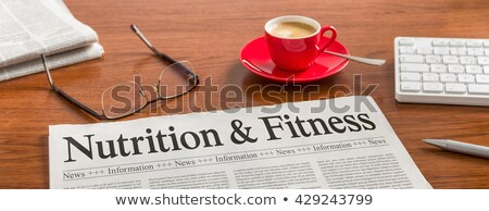 a newspaper on a wooden desk   nutrition and fitness stock photo © zerbor