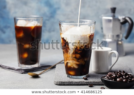 Foto d'archivio: Ice Coffee In A Tall Glass With Cream Poured Over And Coffee Beans On A Grey Stone Background