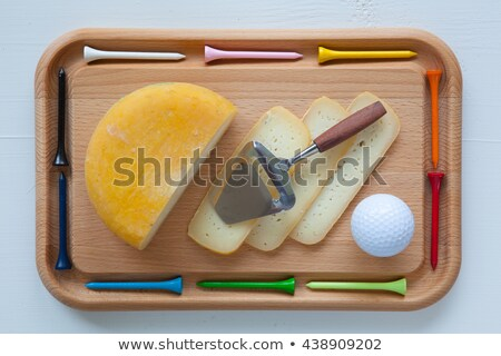 Block of tasty cheese on cutting board with a knife and golf tee Stock photo © CaptureLight