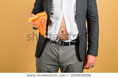 Man With Hand On Stomach Holding Pizza Slice Stock photo © AndreyPopov