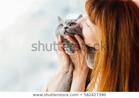 Young woman holding cat close to a window at home Stock photo © Lopolo