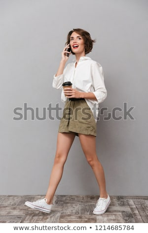 Full length image of gorgeous girl 20s holding takeaway coffee a Stock photo © deandrobot