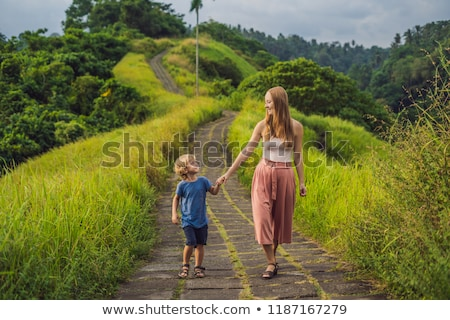 Stock photo: Mom and son tourists in Campuhan Ridge Walk , Scenic Green Valley in Ubud Bali. Traveling with child