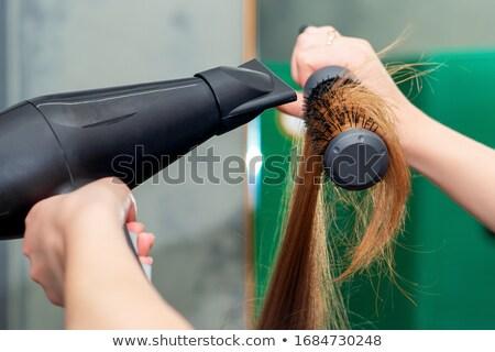 Hand holding hair curling iron round brush Stock photo © manaemedia
