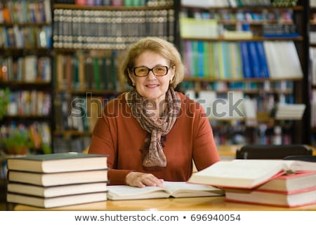 Smiling senior woman sitting on book stack Stock photo © lichtmeister