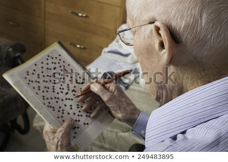 A elderly man sitting doing crosswords hobby Stock photo © Lopolo