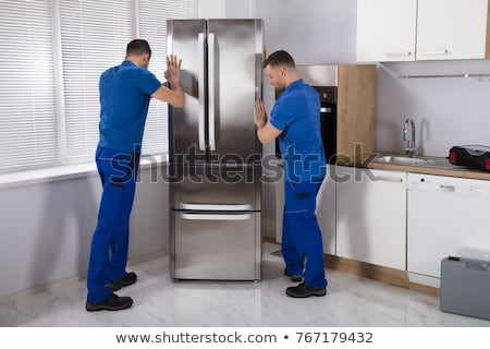 Stock fotó: Two Young Male Movers Placing Steel Refrigerator In Kitchen