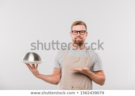 Happy young bearded waiter in apron holding cloche with cooked food Stock photo © pressmaster