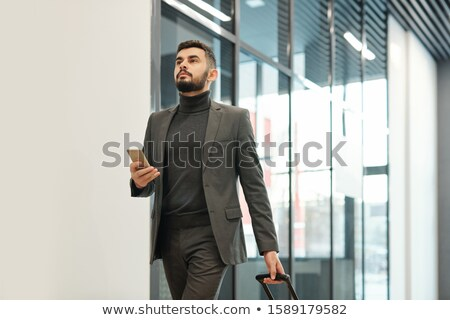 Young businessman in formalwear pulling suitcase while moving towards exit Stock photo © pressmaster