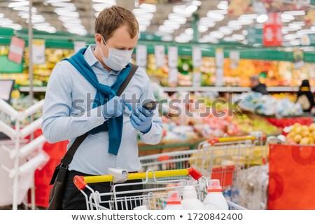 Jeune homme épicerie coronavirus médicaux masque gants Photo stock © vkstudio