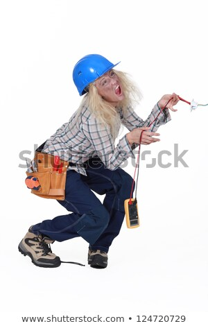 Stock photo: Electrocuted tradeswoman holding a multitester