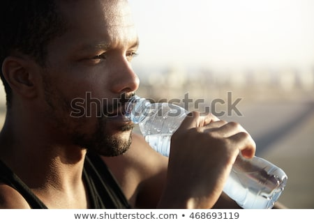 athletic african young man drinking water outdoor stock photo © juniart