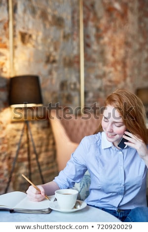 Happy Businesswoman Talking On The Phone And Writing In