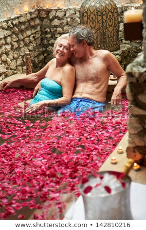 couple relaxing in flower petal covered pool at spa stock photo © monkey_business