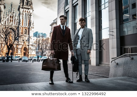 Businessman in black suit posing with bag Stock photo © stockyimages