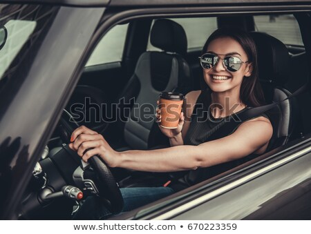 Smiling woman driving car while drinking coffee Stock photo © wavebreak_media