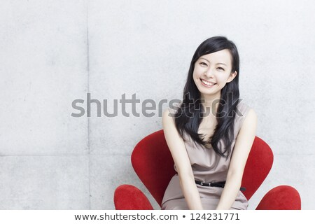 Elegant adult woman sitting in chair against of white modern wall Stock photo © d13
