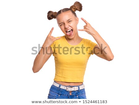funny teenage girl showing tongue and making horns with fingers stock photo © deandrobot