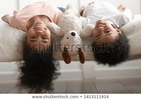 Portrait of happy kid playing upside down indoors in living room Stock photo © zurijeta