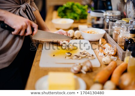 housewife preparing dinner slicing fresh mushrooms stock photo © dash