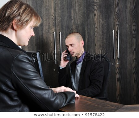 Young man receptionist stands at reception desk front view Stock photo © vectorikart