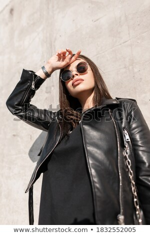 woman in leather jacket standing near grey wall  Stock photo © feedough