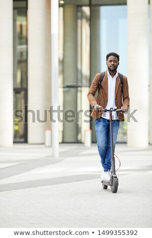 Young african-american man riding scooter. Stock photo © RAStudio