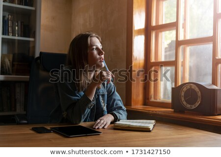 Woman by window writing in a book Stock photo © IS2